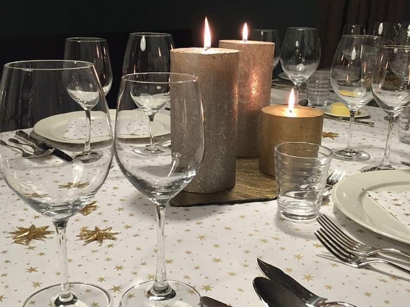 lumanari colorate aprinse, pahare de vin din sicla transparenta