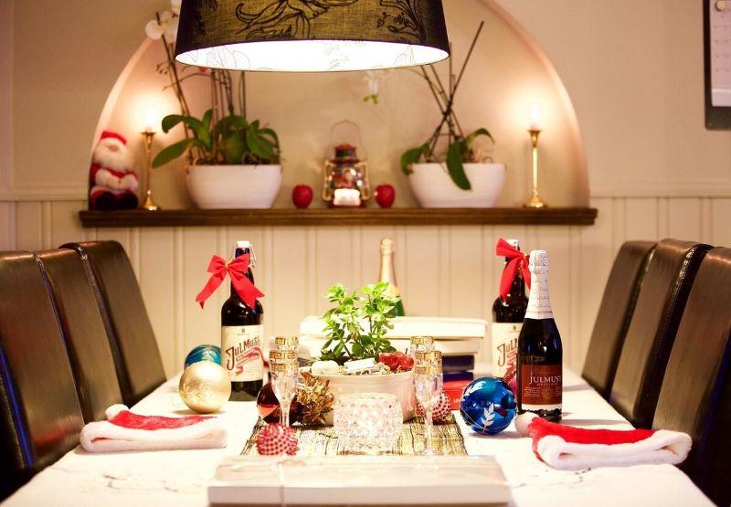 masa de Craciu, sticle de vin, aranjament cu o planta verde, globuri aurii si albastre