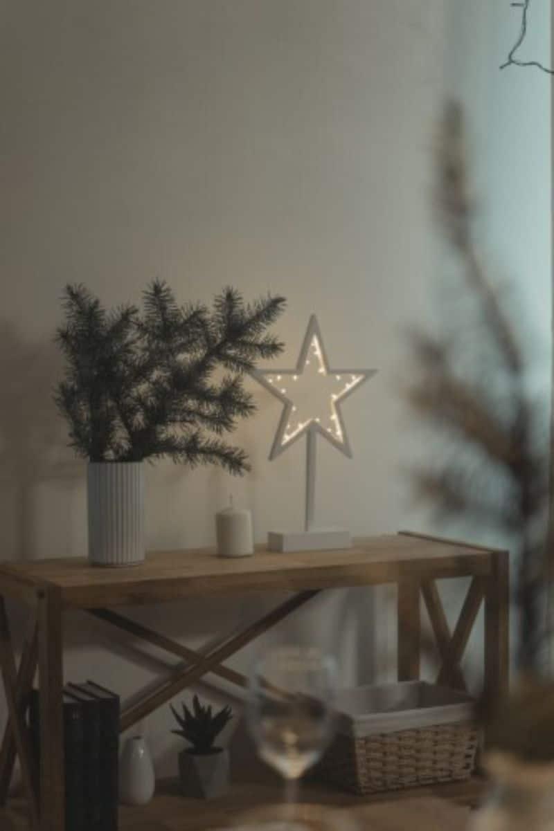 stea din metal cu luminite, creanga de brad in vaza alba pe o balca de lemn