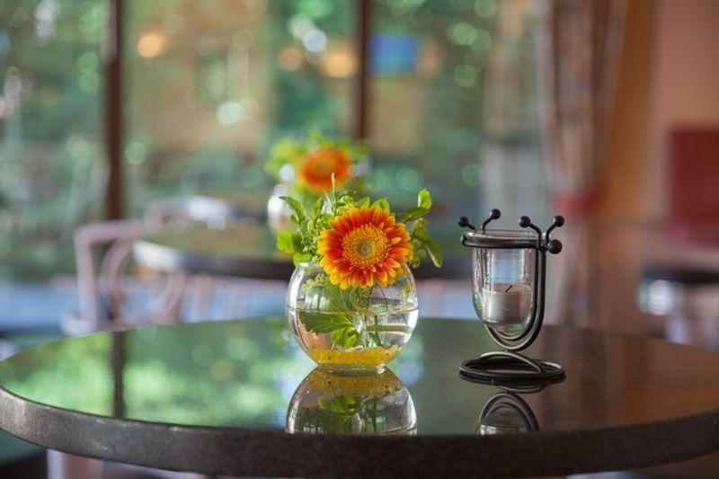 vaza din sticla cu flori galbene cu portocaliu, masa cu o bucata de sticla