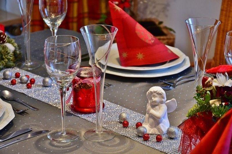 ingeras de portelan alb pe o masa cu aranjamente de Craciun, pahare de sticla