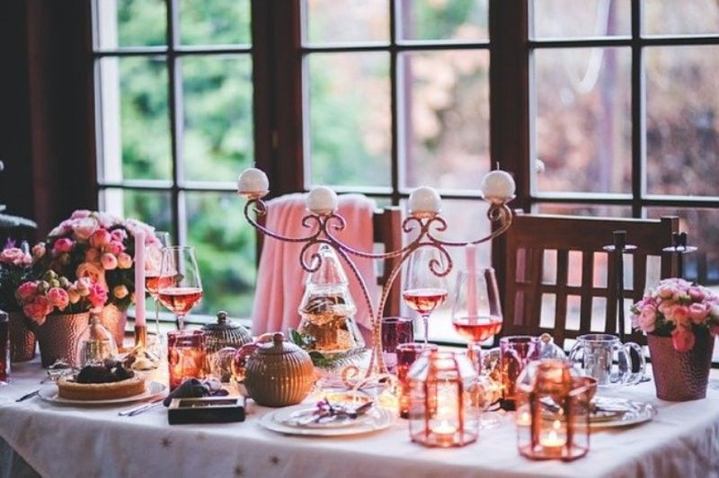 candelabru elegant pe o masa aranjata pentru un eveniment, culoare roz predominanta, pahare de vin rose