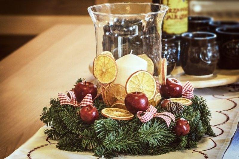 vaza de sticla transparenta cu o lumanare, pe o coronita din crengi de brad, cu bucati de lamaie si mere