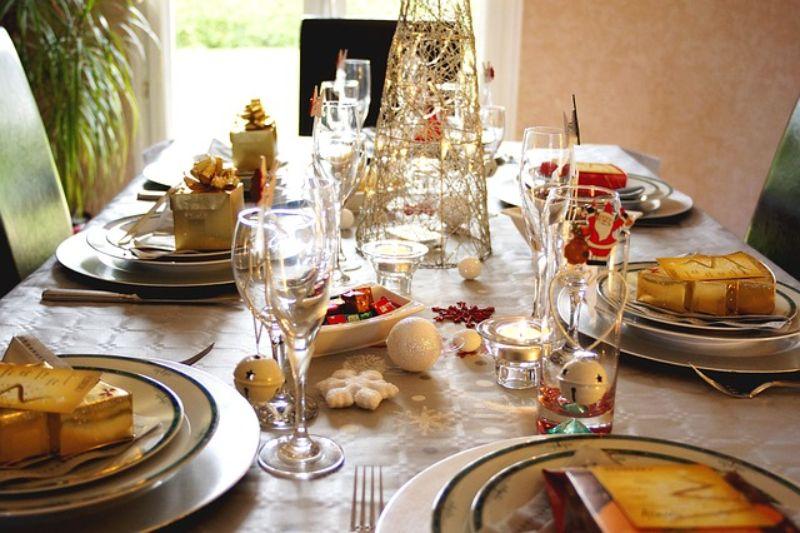 decoratiuni de Craciu pe o masa festiva, cadouri in ambalaje aurii, farfurii albe
