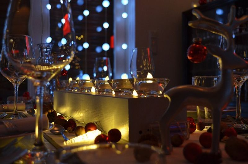 atmosfera de Craciun cu luminite, globulete rosii, pahare de vin