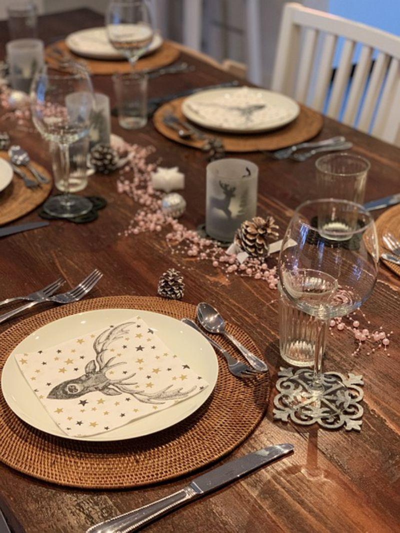 farfurii albe cu servetele cu Reni, masa din lemn, coni de brad