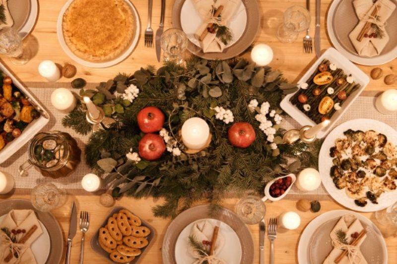 masa festiva de sarbatoare, cu gustari si un aranjament din crengi de braf