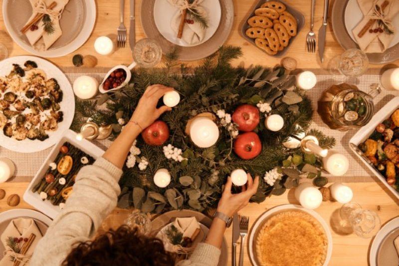coronita de Craciun de us pe masa, rosii si lumanari albe, festin