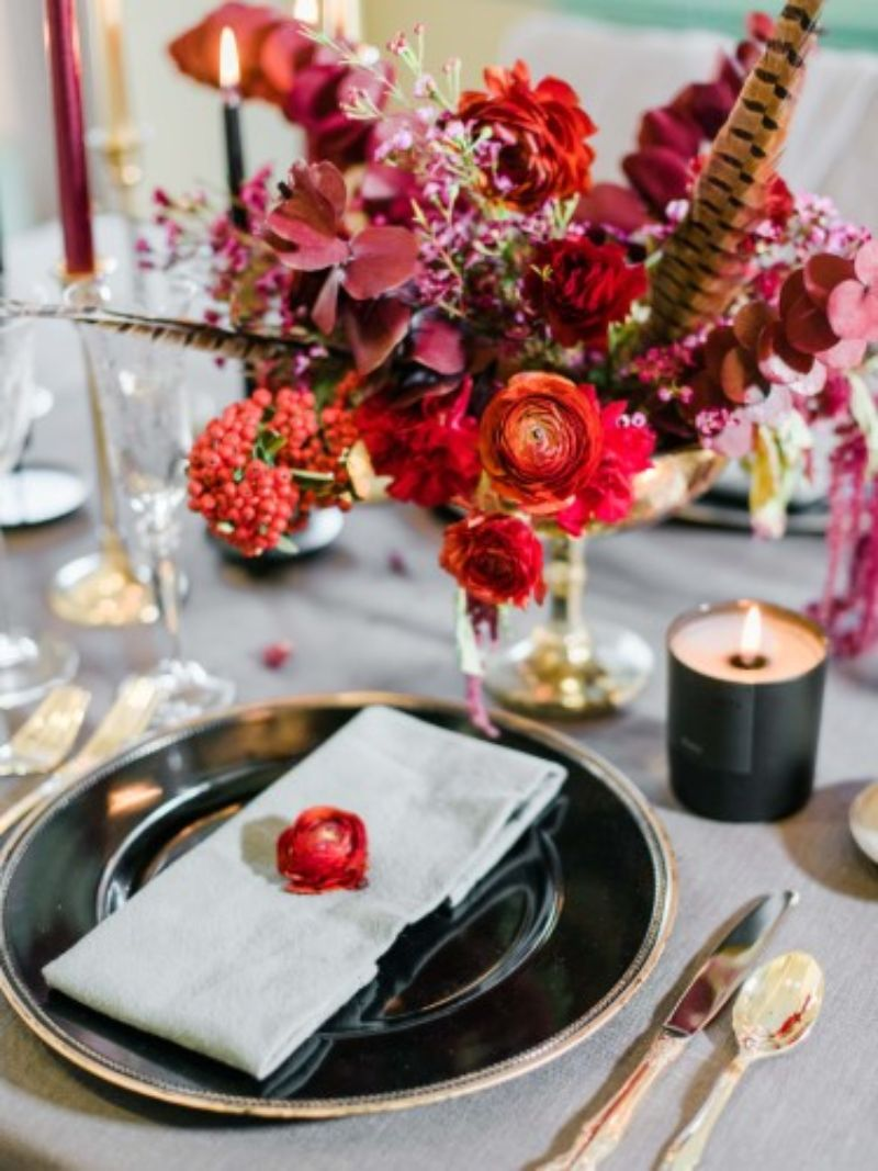 aranjament floral rosu cu mov, facrufie neagra, tacamuri aurii
