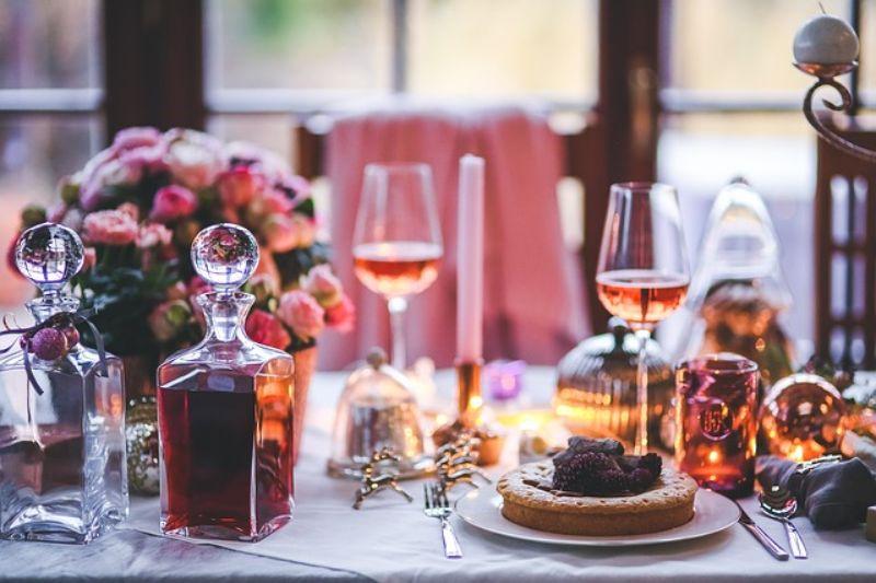 decor de iarna cu o masa festiva, prajitura, pahare cu vin rose