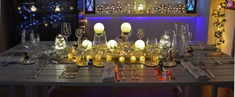 decor cu luminite, cupahare de vine din sticla, pe o masa de lemn