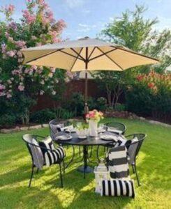 curte amenajata cu plante si copaci, mobilier negru de gradina, umbrela crem