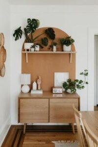 comoda din lemn, decoratiuni albe, plante verzi