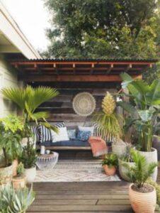terasa cu plante exotice, ghivece maro, canapea cu perne colorate