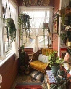 balcon amenajat cu plante agatate, fotoliu de culoarea mustarului, fundal colorat