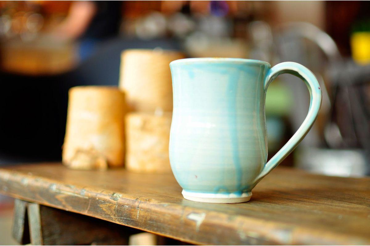 Cana din ceramica, culoarea albastru deschis, masa din lemn masiv