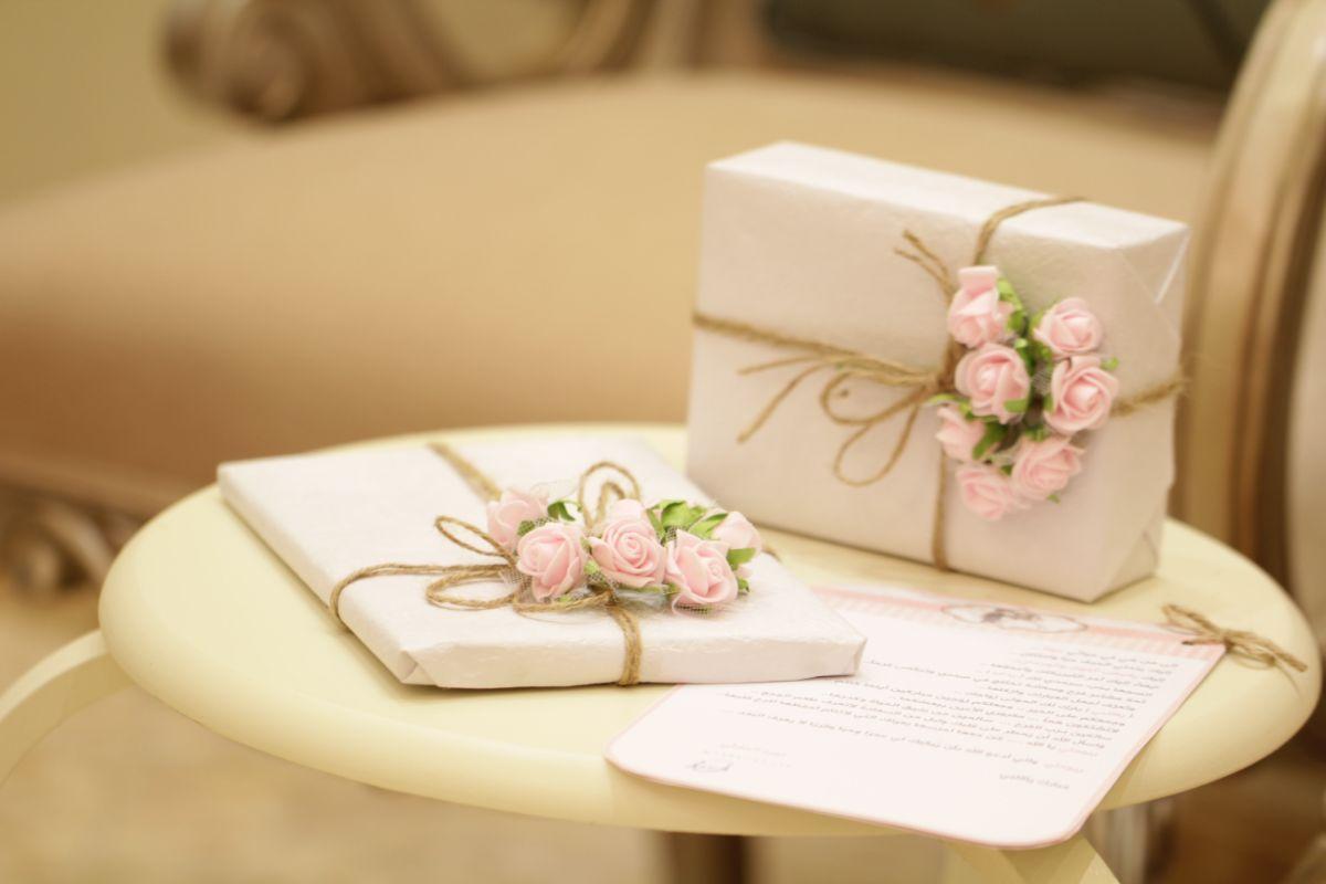 Cadouri impachetate cy hartie crem si funie maro, trandafiri roz, masuta din lemn