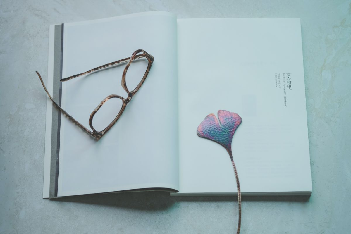 carte deschisa cu pagini albe, ochelari de vedere