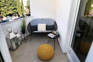 Balcon amenajat simplu, taburete galben mustar, masuta de cafea cu o plamta om ghiveci