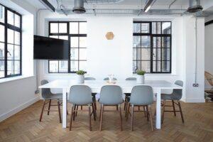 Masa alba de living, scaune gri, ferestre cu margini negre, podea din lemn