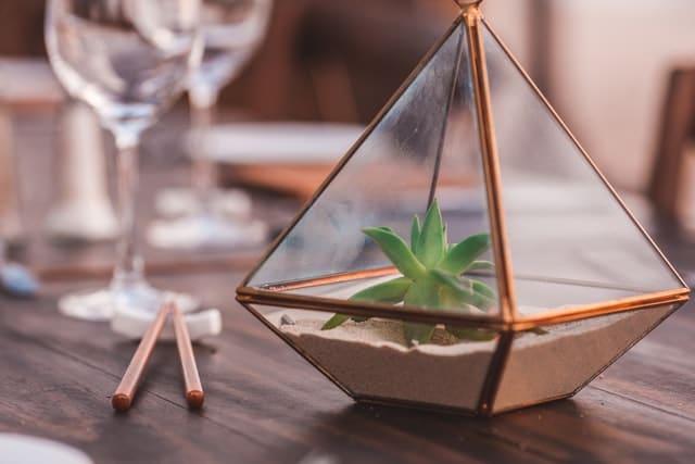 piramida din sticla cu profile de alama, pe o masa din lemn cu pahare de vin goale pe ea, nisip crem