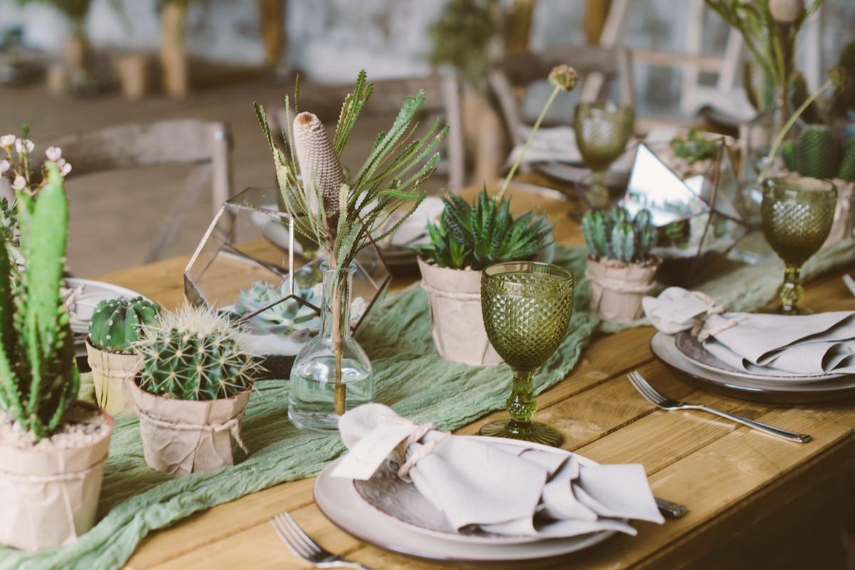 aranjarea unei mese festive cu plante verzi, forme geometrice, servetele roz pas,