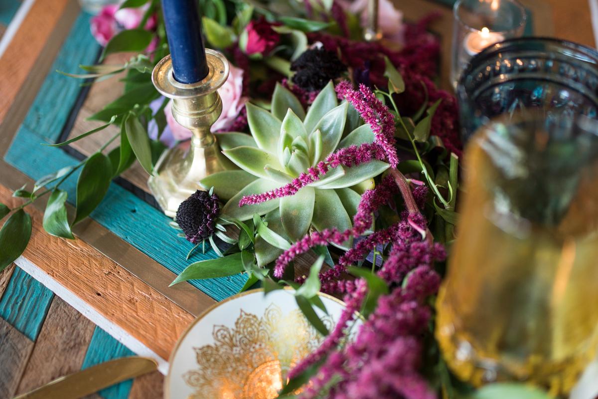 decor cu planta suculenta pentru un eveniment, sfesnis auriu cu lumanare albastra, masa din lemn