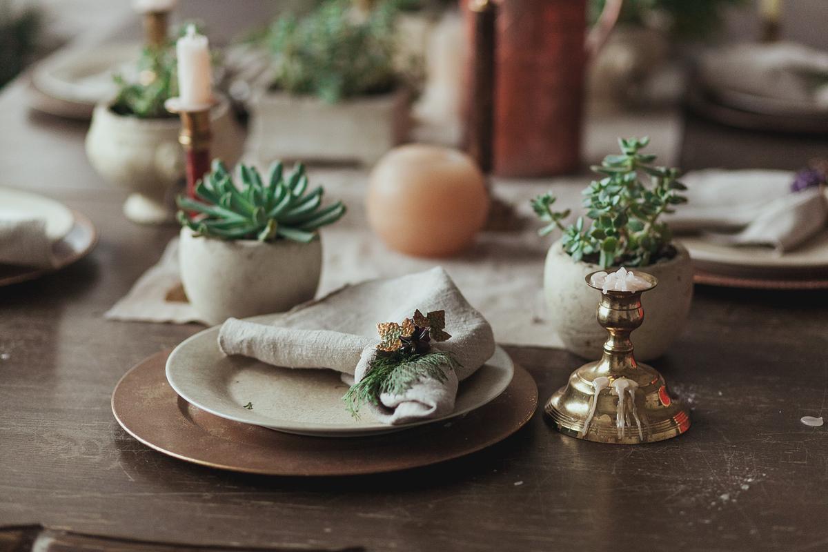 masa de eveniment aranjata cu farfurii de culoarea pamantului, plante suculente in ghivece din ceramica, sfesnic cu lumanare topita