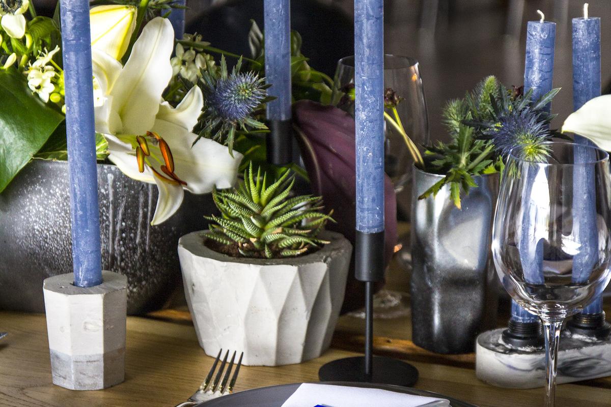 aranjarea unei mese festive cu plante suculente, ghivece gri, lumanari albastre