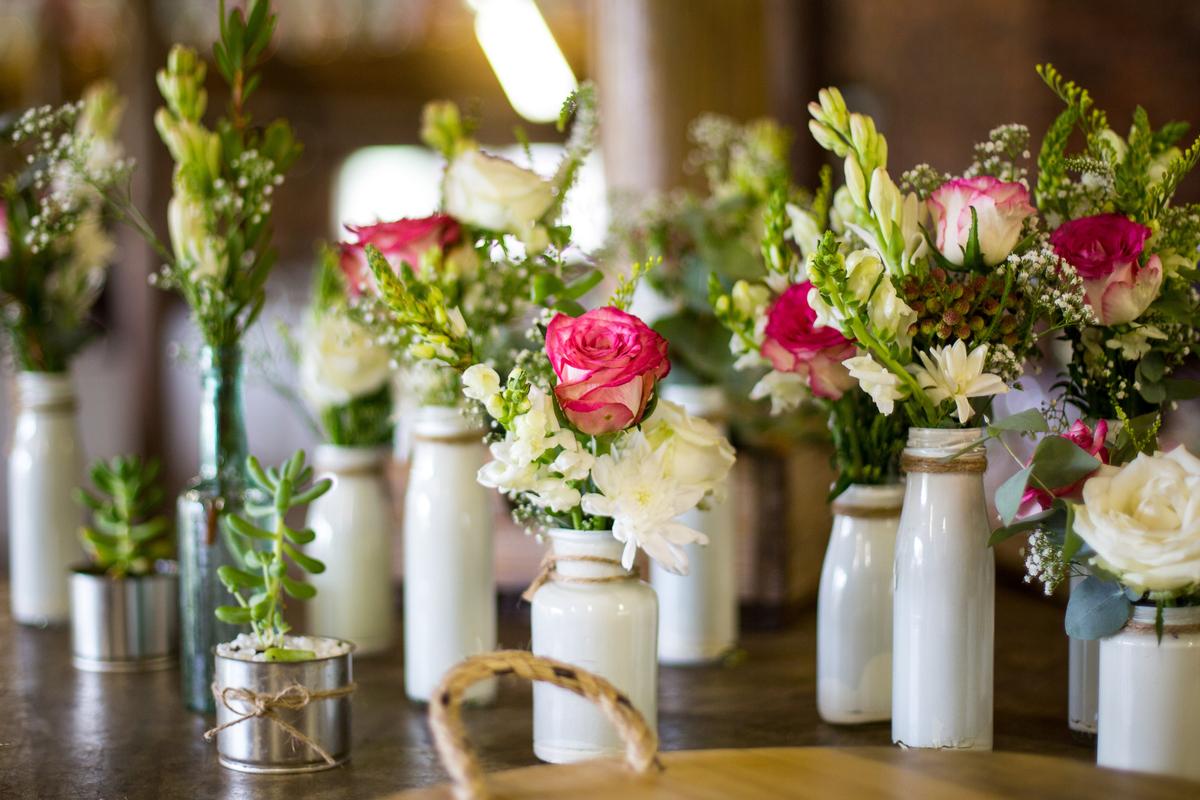 buchetele de flori in sticle albe, aranjamente nunta, masa din lemn