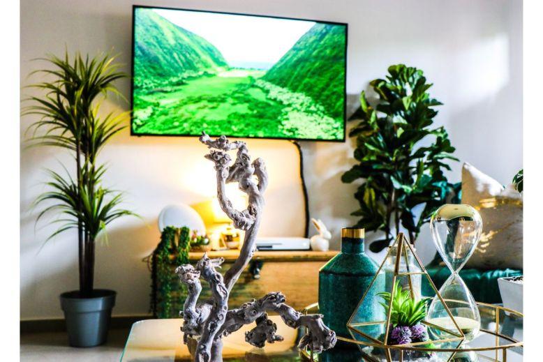 decoratiuni pentru masa din living cu un terariu din sticla, o vaza turcoaz, o clepsidra, o decoratiune ca niste corali, fundal de natura cu plante verzi