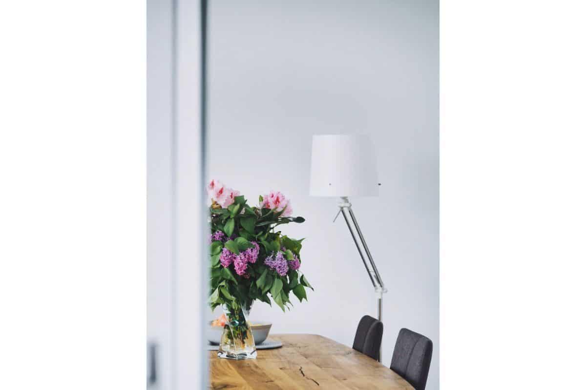 flori de liliac moc pe o masa masiva din lemnb, lampa cu abajur alb