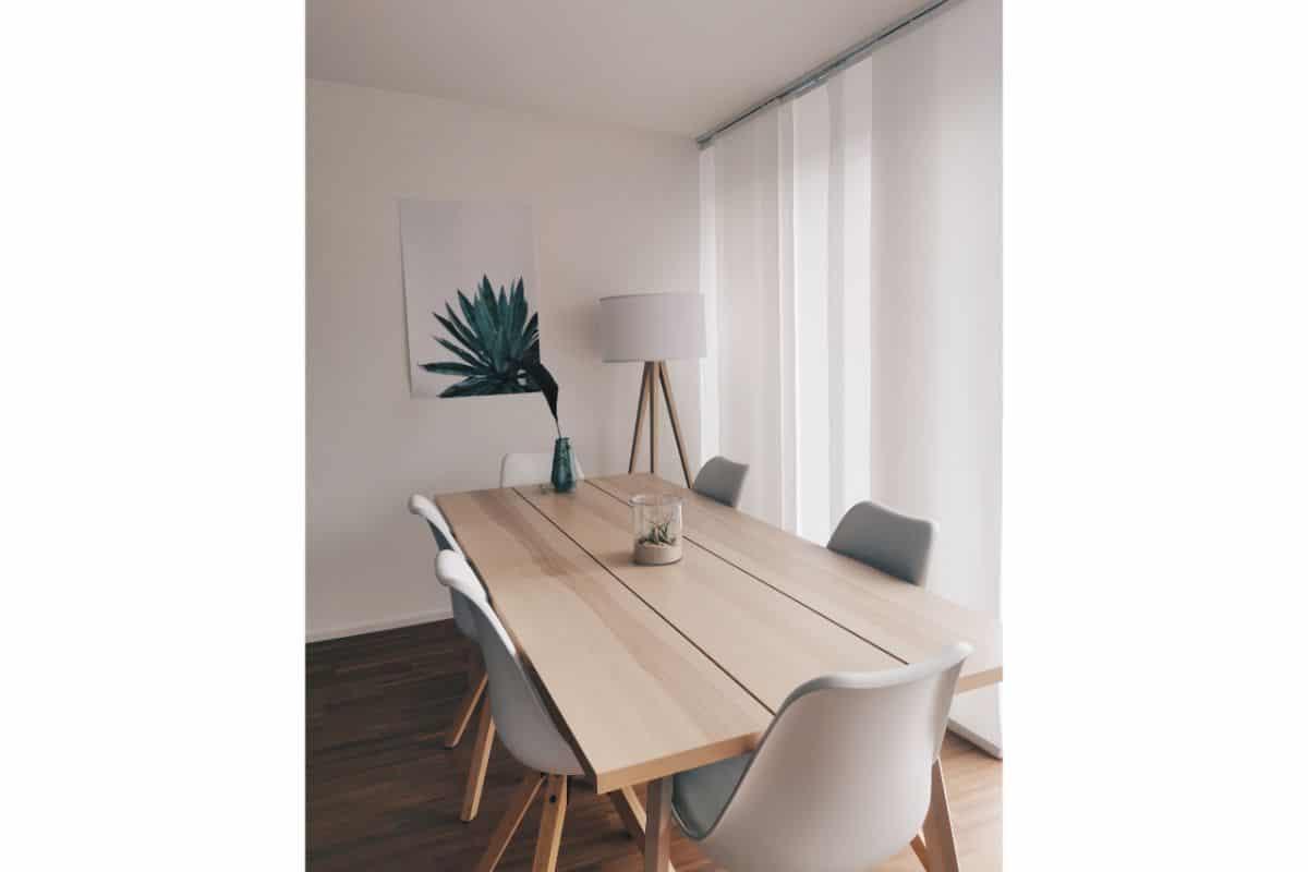 masa de living din lemn de culoare deschisa, scaune albe cu picioare din lemn, tablou cu o planta verde