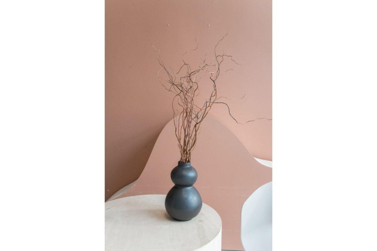 Vaza gri cu forme rotunde si crengi de copac in ea, masa alba, fundal roz
