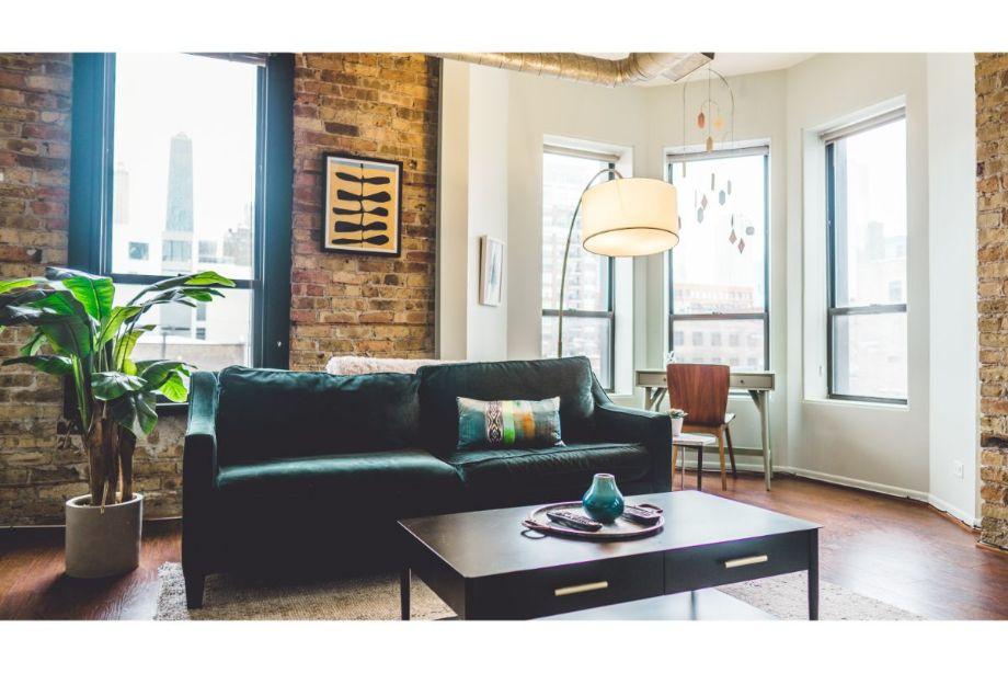 colt de relaxare intr-o sufragerie, canapea de culoare inchisa si masa de living din lemn, planta verde, perete cu caramida, colt pentru lucrat