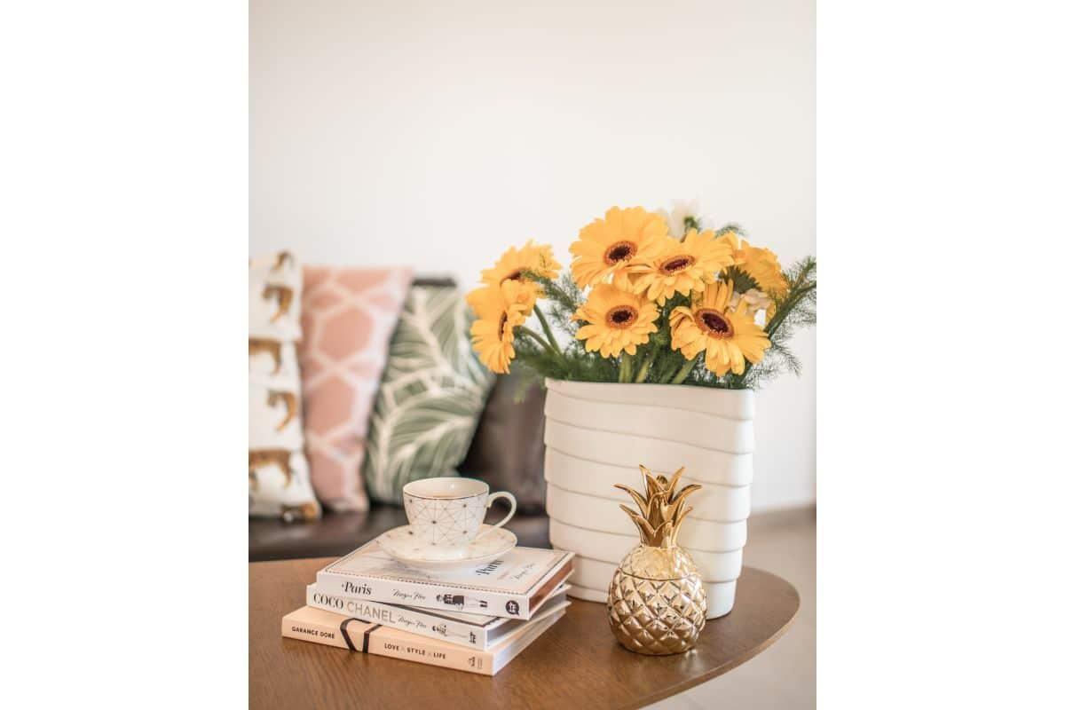 masa de living din lemn cu carti de citit si cana de cafea pe ea, cu flori galbene in ghiveci alb