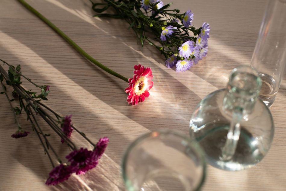 Flori de primavara de culoarea mov, roz si visiniu, carafa din sticla cu apa