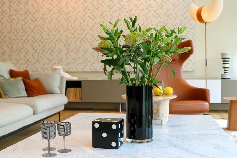 Masa de living cu flori verzi in ghiveci de sticla, un zar de dimensiuni mari, masa din marmura sau granit, fotoliu din piele