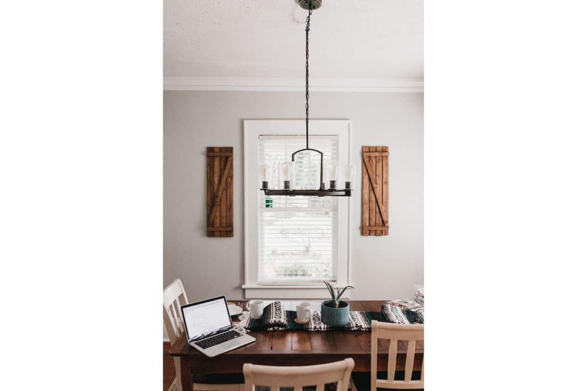 Masa din lemn perfecta pentru lucrat de pe laptop, planta verde in ghiveci cu cani de ceai pe langa, scaune din lemn, fundal alb