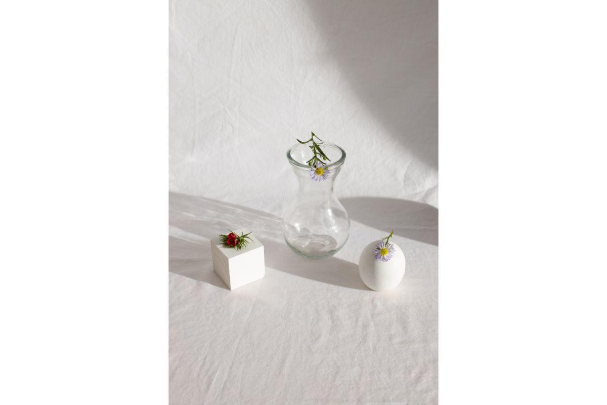 flori colorate puse pe trei produse diferite, vaza de sticla, cub alb si bila alba