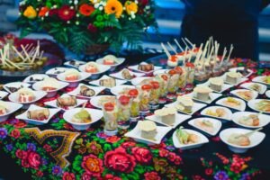 bufet suedez cu mancaruri alese, pe o masa cu o fata de masa cu motive florale de diferite culori