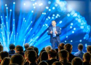 Eveniment cu oameni, vorbitor in fata unui ecran mare cu proiectii de culoare albastra