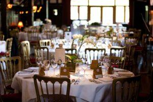 Masa aranjata pentru un eveniment, cu mici cadouri la fiecare scaun si detalii minutioase