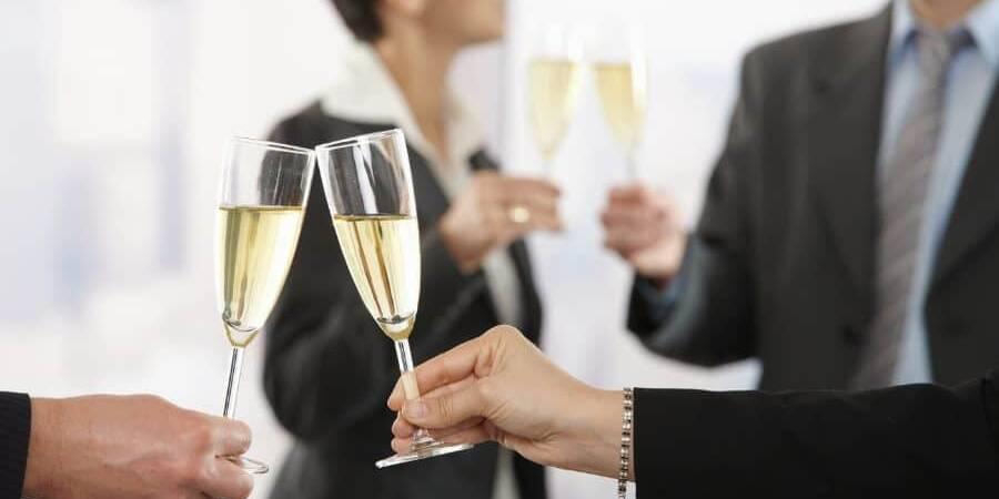 2 pahare de sampanie ciocnite de un barbat si o femeie, sarbatoresc un eveniment, in fundal sunt alti 2 oameni cu pahare de sampanie
