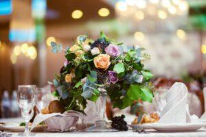 buchet de trandafiri colorati cu verdeata, pe o masa aranjata pentru un eveniment, fundal blurat