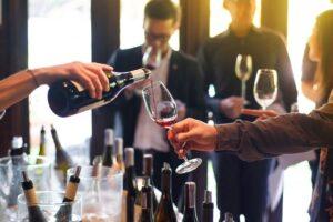 Pahar de vin umplut cu un vin rosu, fundal blurat cu oameni care discuta si gusta vin, sticle de vin, eveniment