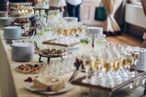 Arsnjarea unei mese de la un eveniment corporate, prajituri, sampanie, vesela